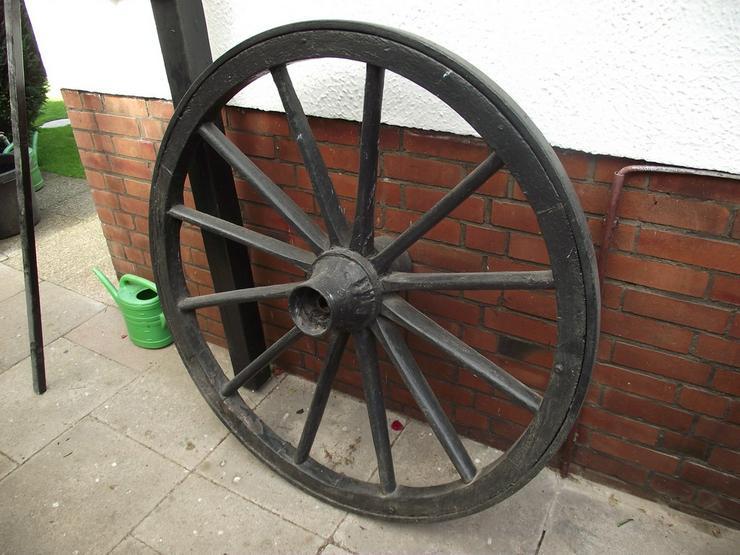 Altes Wagenrad mit Kutschgeschirrteilen