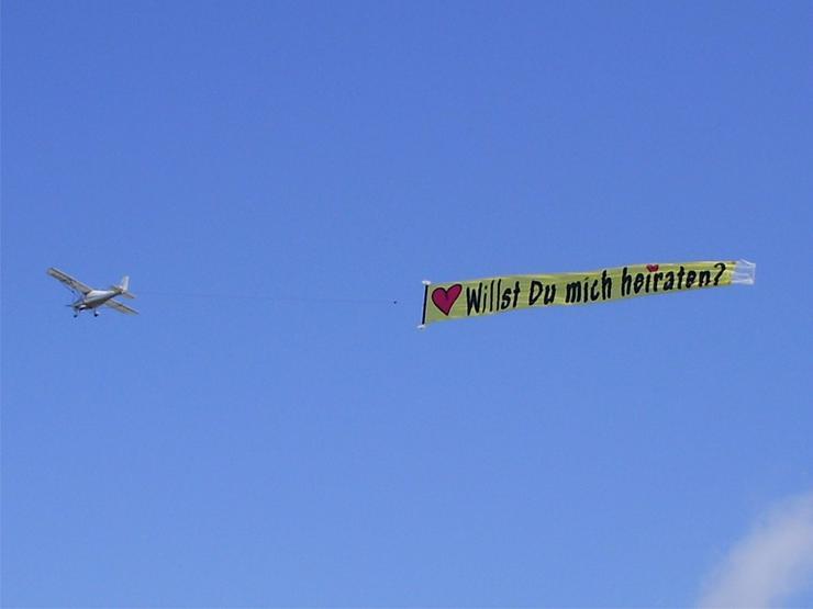 Heiratsantrag aus der Luft mit Flugzeugbanner